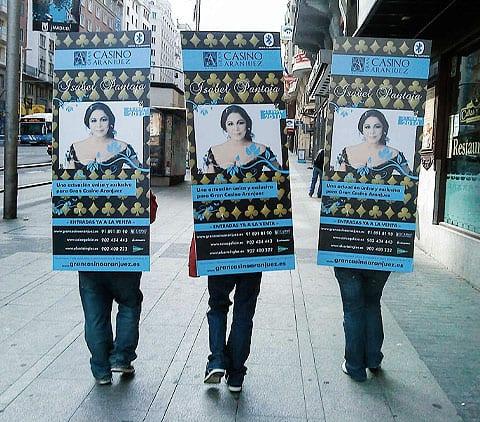 tres azafatas haciendo publicidad en la calle con un cartel en la espalda en madrid