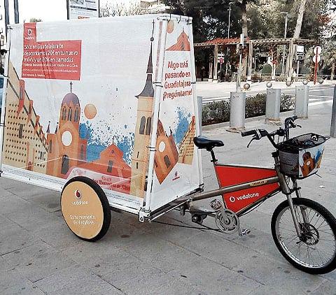 triciclo extra grande llamado mupi bike haciendo publicidad de vodafone en la calle de valencia