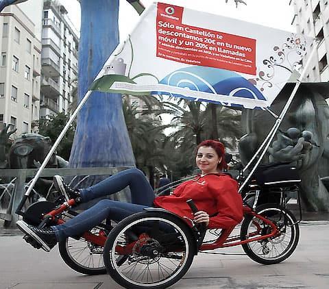 bicicleta con 3 ruedas haciendo publicidad de vodafone en la calle con una azafata