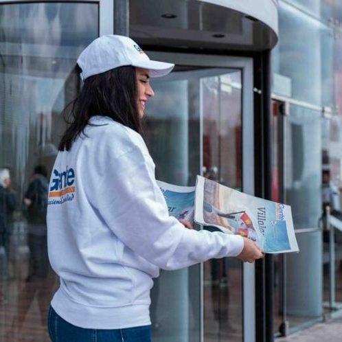 chica repartiendo publicidad en la calle a una señora