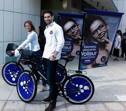 bicicleta con publicidad en una bandera y en las ruedas junto a dos azafatos