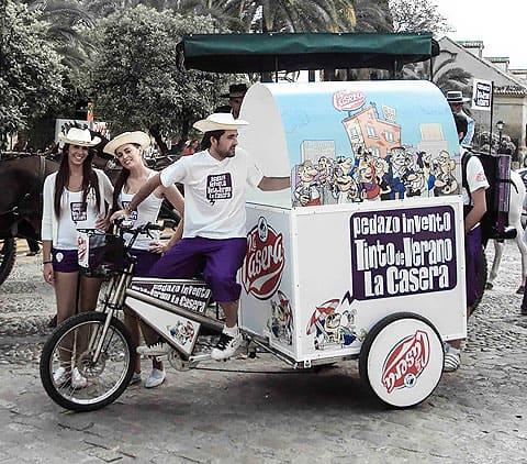 bicicleta con cajon haciendo publicidad de la casera y 4 azafatas